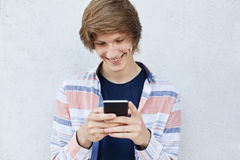 Cheerful teenager with trendy hairstyle holding modern smart phone typing messages or playing games online smiling pleasantly havi. Ng dimples on his face Stock Photography