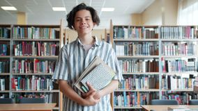 Cheerful teenager walking in college library holding books looking at camera. Cheerful teenager handsome boy is walking in college library alone holding books stock footage