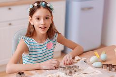Cheerful teenager working with dough in the kitchen. Romantic style. Cute kid expressing positivity while looking at camera royalty free stock photography