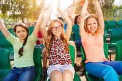 Cheerful teenagers hold arms up during game. At the stadium sitting on the tribune outside in summer Royalty Free Stock Photo