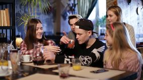 Cheerful teenagers relaxing at coffee shop. Group of young friends sitting in cafe, chatting and having fun. Handsome hipster mixing two kinds of juice and stock video footage