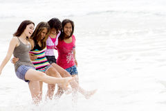 Cheerful teens. Group of cheerful teens girls playing on beach Stock Images