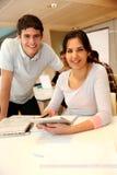 Cheerful teens in classroom Stock Image
