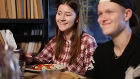 Cheerful teens enjoying meal sitting at cafe table stock video