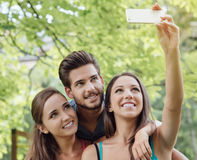 Cheerful teens at the park taking selfies. Cheerful smiling teens at the park sitting on a bench and taking selfies using a smart phone Royalty Free Stock Photography