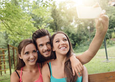 Cheerful teens at the park taking selfies. Cheerful smiling teens at the park sitting on a bench and taking selfies using a smart phone Stock Photography