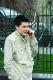Cheerful telephone talk. Young  man talking by cell mobile phone Royalty Free Stock Photos