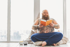 Cheerful thick guy enjoying literature Royalty Free Stock Images