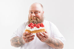 Cheerful thick guy presenting his favorite unhealthy food Royalty Free Stock Image