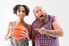 Cheerful thick male hipster is friendly to weak guy. This is the real friend. Excited fat men with beard is pointing finger are smiling thin boy. They are Stock Image