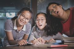 Cheerful three asian teenager doing school work in home living stock images