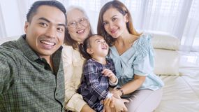 Cheerful family takes a group picture at home royalty free stock image