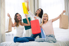 Cheerful three girlfriends with many shopping bags Stock Photography