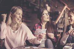 Three girls at home playing cards. royalty free stock image