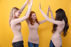 Cheerful three ladies give a high five to each other. Photo of young cheerful three ladies standing over yellow background give a high five to each other Royalty Free Stock Image