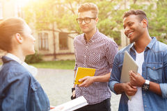 Cheerful three students are chatting in campus royalty free stock images