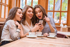 Cheerful three women using smartphone Stock Images