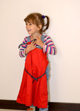 The cheerful three-year-old girl tries on on herself a beautifulred dress on a hanger Stock Images