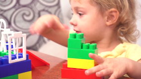 Cheerful toddler girl building house. From plastic blocks sitting at the table stock video footage