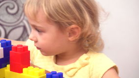 Cheerful toddler girl building house. From plastic blocks sitting at the table stock footage