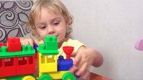 Cheerful toddler girl building house. From plastic blocks sitting at the table stock video