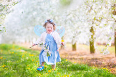 Cheerful toddler girl in fairy costume in blooming garden Stock Photo