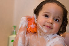 Cheerful toddler scrubbin in the tub Stock Images
