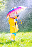 Cheerful toddler with umbrella playing in the rain. Funny cute curly toddler girl wearing yellow waterproof coat and boots holding colorful umbrella playing in Stock Image