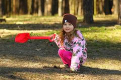 Cheerful todler girl showing the way in the forest with a red shovel Stock Photos