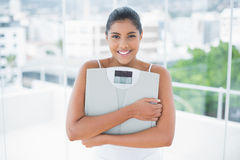 Cheerful toned brunette holding scales Royalty Free Stock Photos