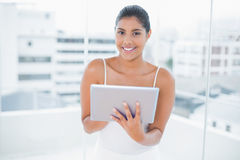 Cheerful toned brunette holding tablet Royalty Free Stock Image