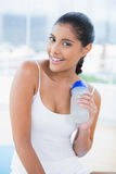 Cheerful toned brunette sitting on floor with sports bottle Royalty Free Stock Images