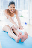 Cheerful toned brunette sitting on floor stretching legs Stock Photography