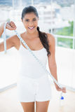 Cheerful toned brunette stretching measuring tape Stock Image