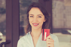 Cheerful toothy smile woman holding showing loyalty card near store shopping mall outdoors in street. Shopaholic concept pay with credit card banking Stock Images
