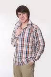 Cheerful toothy young man in checked shirt and smart casual wear. Looking at camera and holding hands in pockets while standing isolated on studio white Royalty Free Stock Images