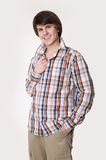 Cheerful toothy young man in checked shirt and smart casual wear. Looking at camera and holding hands in pockets while standing isolated on studio white Royalty Free Stock Image