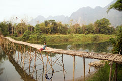 Cheerful Tourist crossing bamboo bridge, limestone view, laos Stock Images