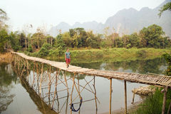 Cheerful Tourist crossing bamboo bridge, limestone view, laos Royalty Free Stock Photos