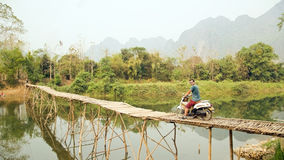 Cheerful Tourist crossing bamboo bridge motorbike, limestone view, laos Stock Image