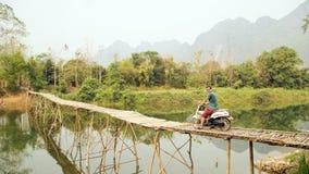 Cheerful Tourist crossing bamboo bridge motorbike, limestone view, laos Stock Image
