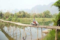 Cheerful Tourist crossing bamboo bridge motorbike, limestone view, laos Stock Photography