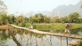 Cheerful Tourist crossing bamboo bridge motorbike, limestone view, laos Stock Images