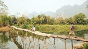 Cheerful Tourist crossing bamboo bridge motorbike, limestone view, laos Stock Images