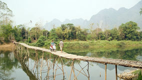 Cheerful Tourist crossing bamboo bridge motorbike, limestone view, laos stock photos