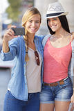 Cheerful tourist female friends taking photos themselves Stock Image