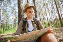 Cheerful tourist preparing for travel. Joyful young man is reading a map and smiling. He is sitting in forest with touristic equipment Royalty Free Stock Photos