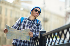 Cheerful Tourist Sightseeing in City. Portrait of modern young man  holding map traveling alone in Europe sightseeing in streets of old city Stock Photography