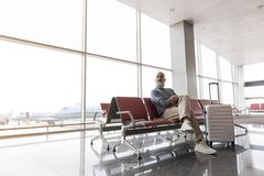 Happy smiling passenger waiting for flight Royalty Free Stock Photo