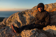 Cheerful tourist welcomes sunrise on top of mountain Ilyas Kaya. Royalty Free Stock Photos